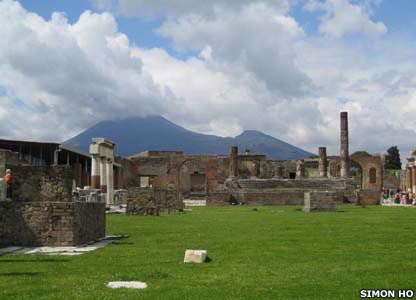 Mount Vesuvius looms threateningly in the background behind the ruins of the Temple of Jupiter